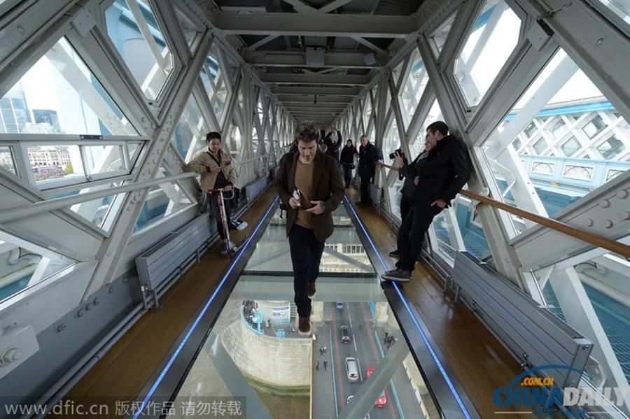 当地时间2014年11月11日,英国伦敦,作为伦敦著名的旅游景点之一,伦敦塔桥日前再添新景观,伦敦塔桥上桥的玻璃地板通道修建完成,并对游客开放。据悉,此次改造完成的玻璃地板位于塔桥上桥,玻璃地板长约11米,宽约1.8米,由6块钢化玻璃板排列组成。据塔桥负责人介绍,此次改造工程历时2年,耗资100万英镑,游客可以透过玻璃地面360度俯瞰泰晤士河和两岸美景。据报道,伦敦塔桥是从泰晤士河口算起的第一座桥,将伦敦南北区连接成整体,是伦敦的象征,有伦敦正门之称。塔桥始建于1886年,1894年建成通车并对公众开