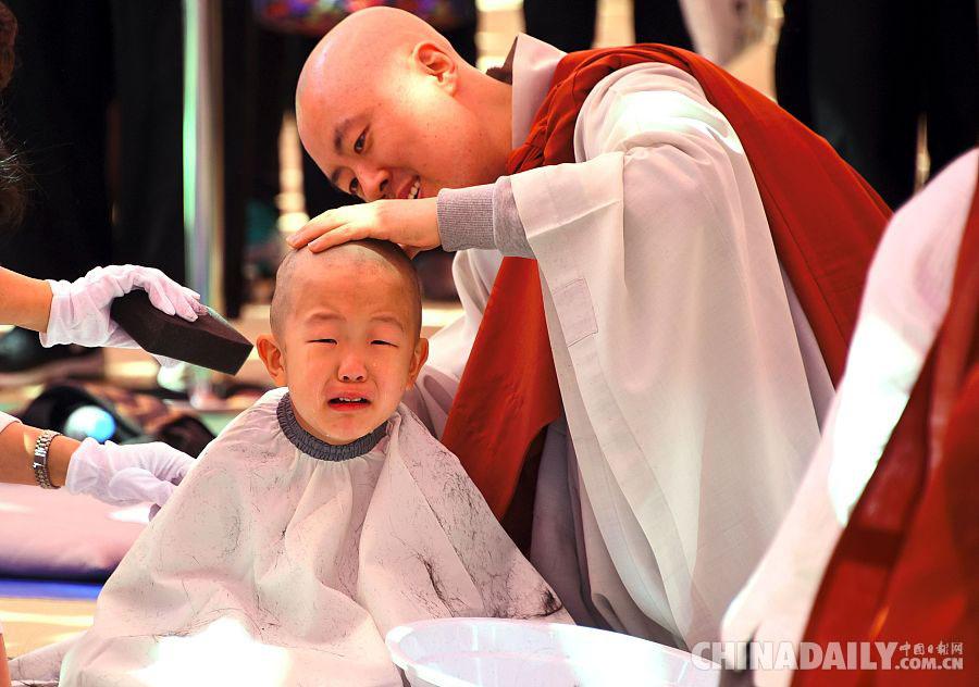 一个小和尚在剃度时大哭起来,看来他很舍不得自己的头发.