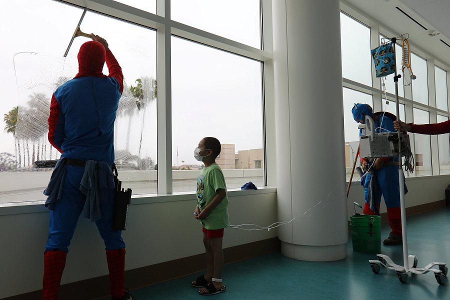 """美国:清洁工变身""""超级英雄""""擦玻璃 逗乐患病儿童"""