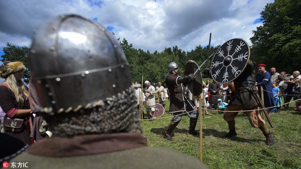 """参与者身着中世纪服饰,男人们手持冷兵器""""对战"""",女人们则和孩子在帐篷"""